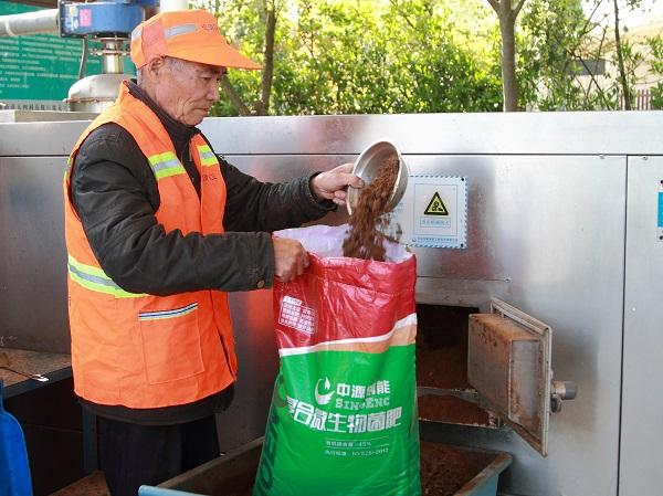 4.变废为宝-工人把复合微生物菌肥装袋.JPG